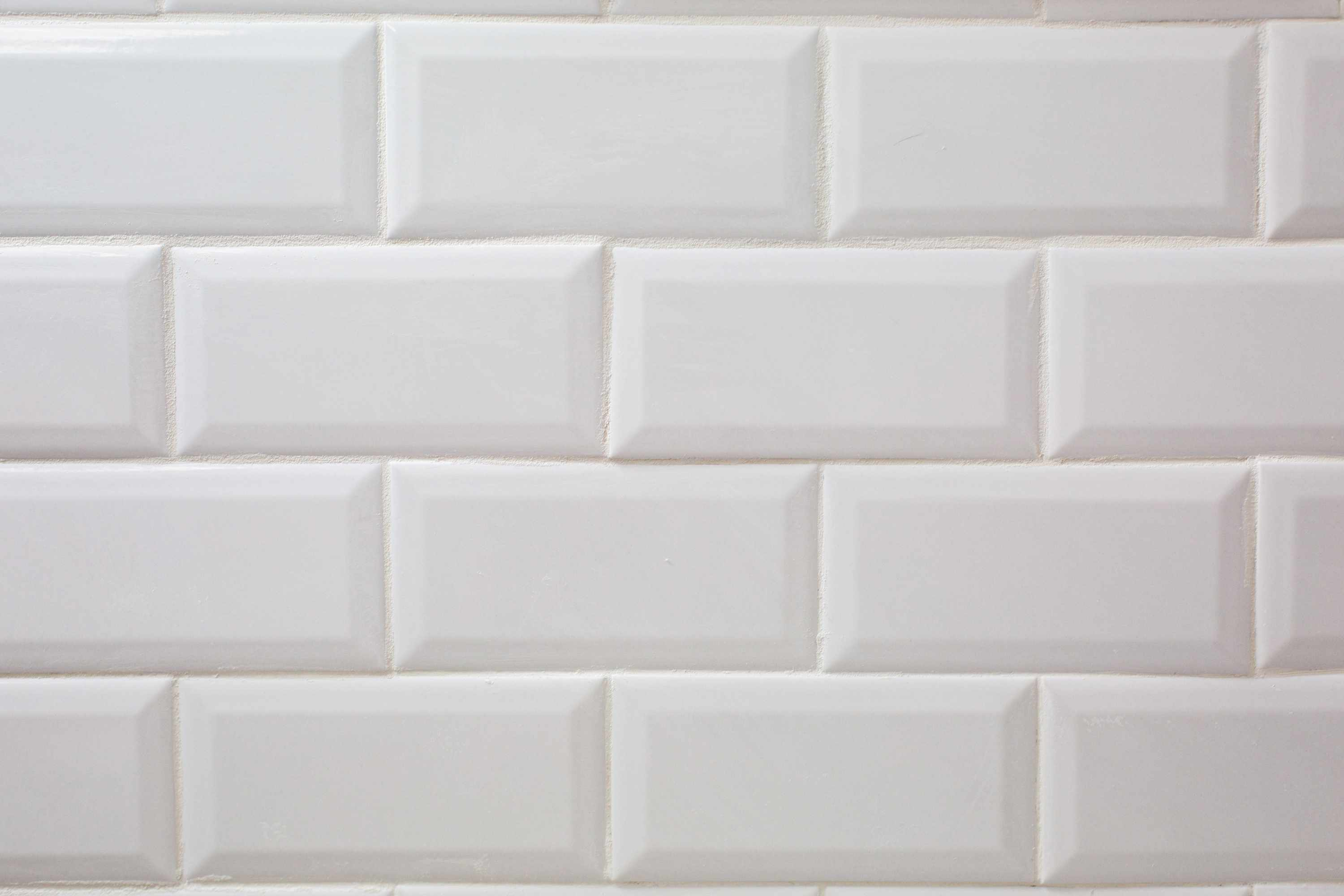 White tiled wall with cured grout