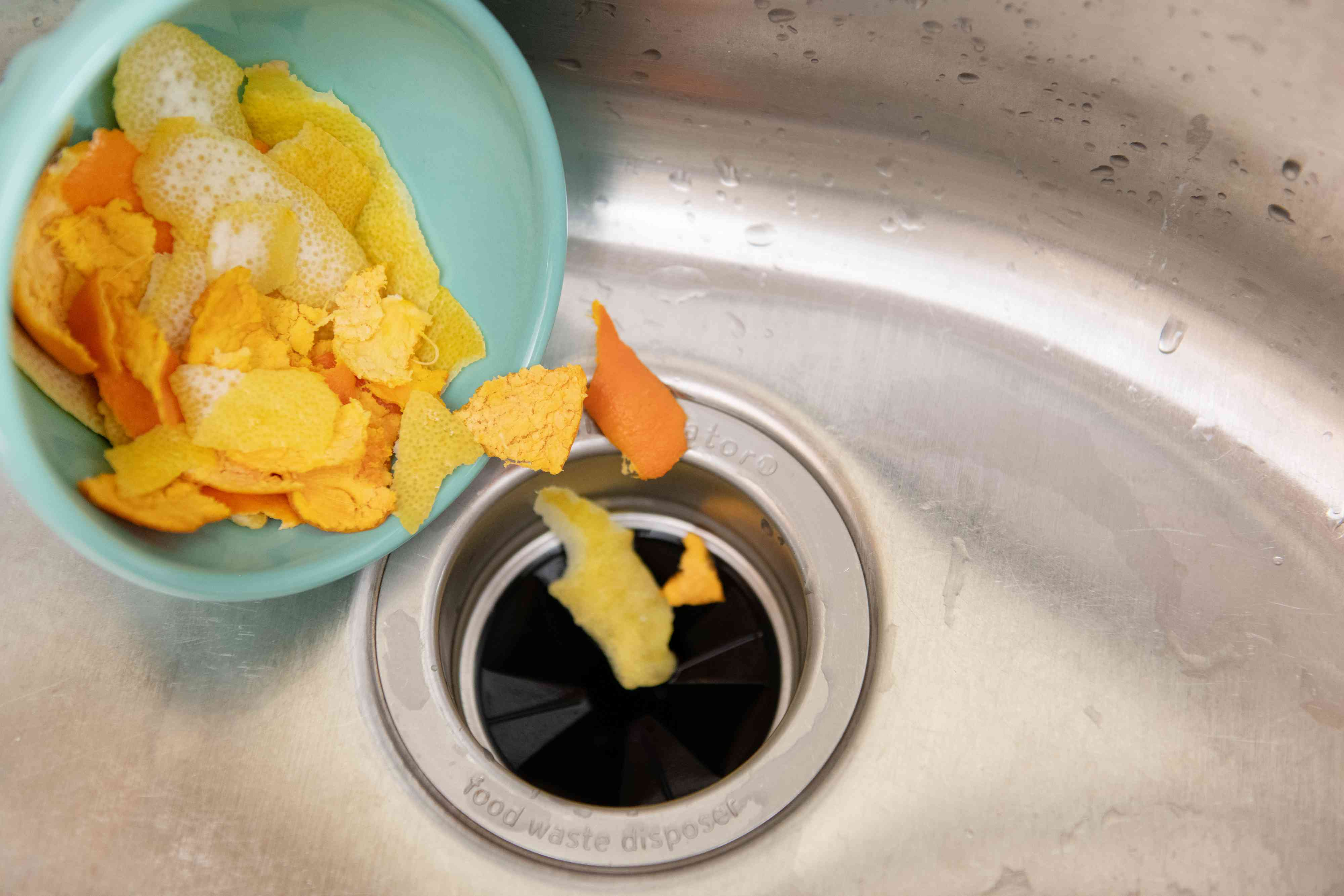 pouring citrus peels down a garbage disposal
