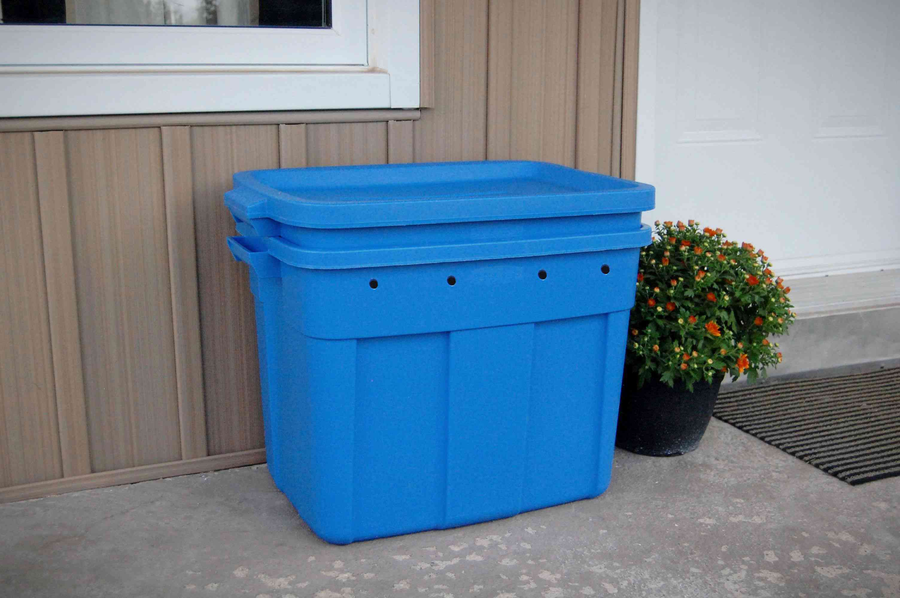 Compost bin outside of a storage shed