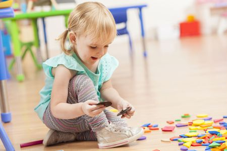 Cute Toddler Girl Playing With Toys On Floor