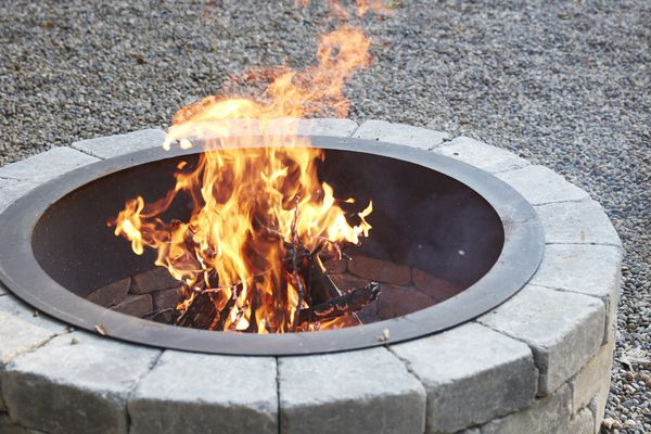 Light gray stone and round fire pit with fire inside
