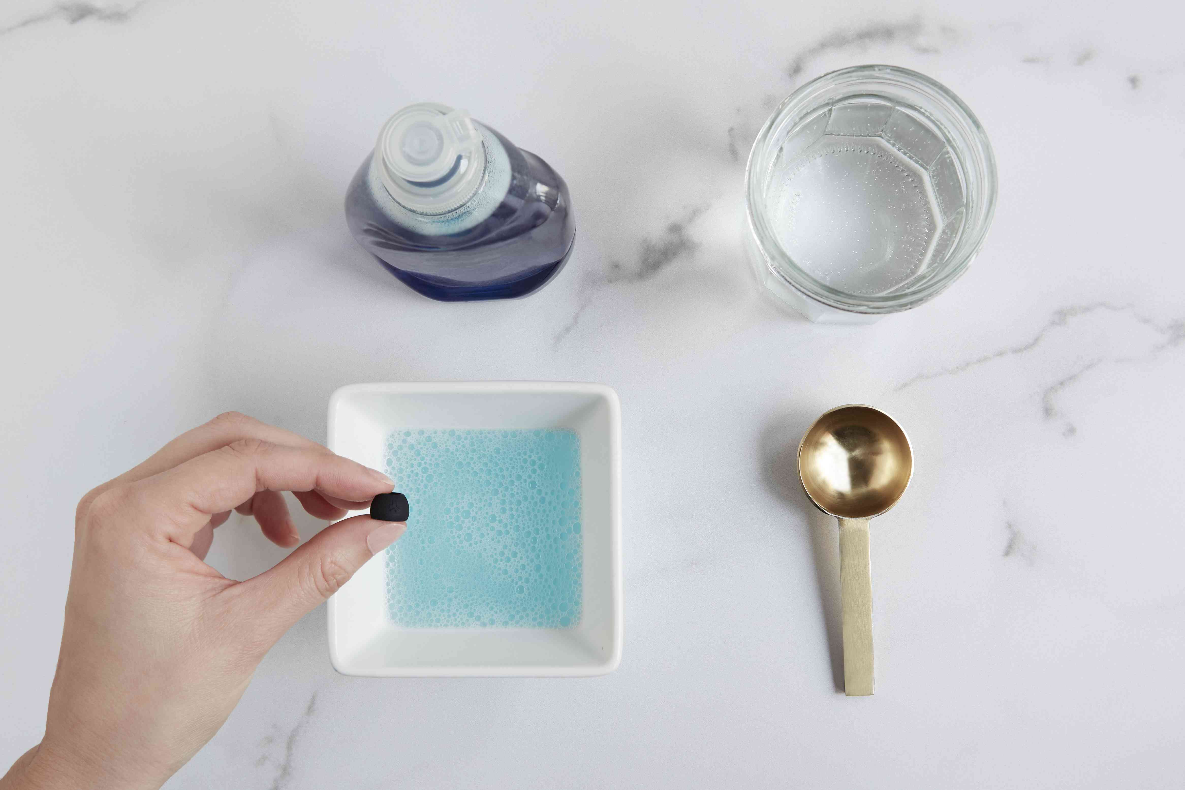 person cleaning the earbud tips in soapy mixture