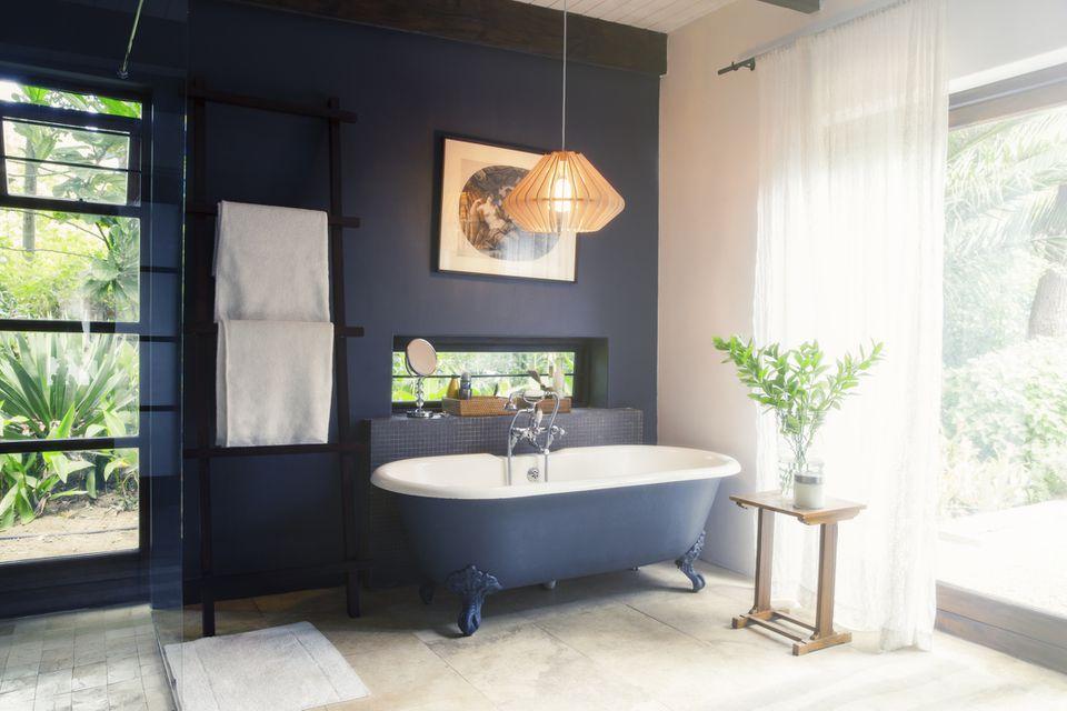 Pared de baño azul marino con bañera con patas a juego