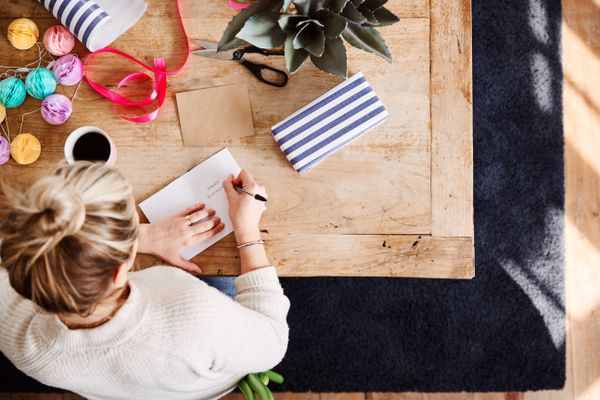 Overhead Shot Looking Down On Woman At Home Writing In Birthday Card And Wrapping Gift