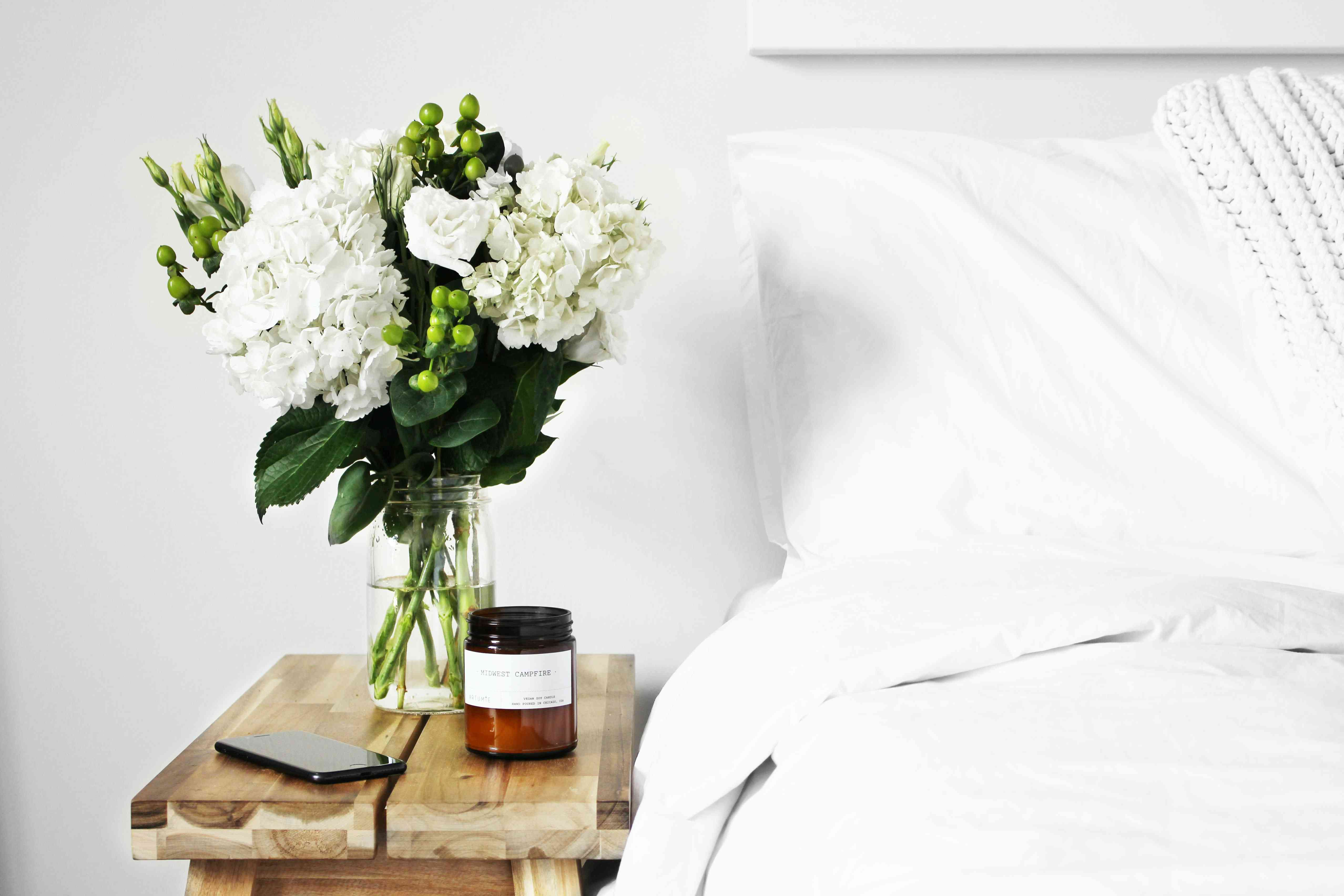 White bed linens and white flowers