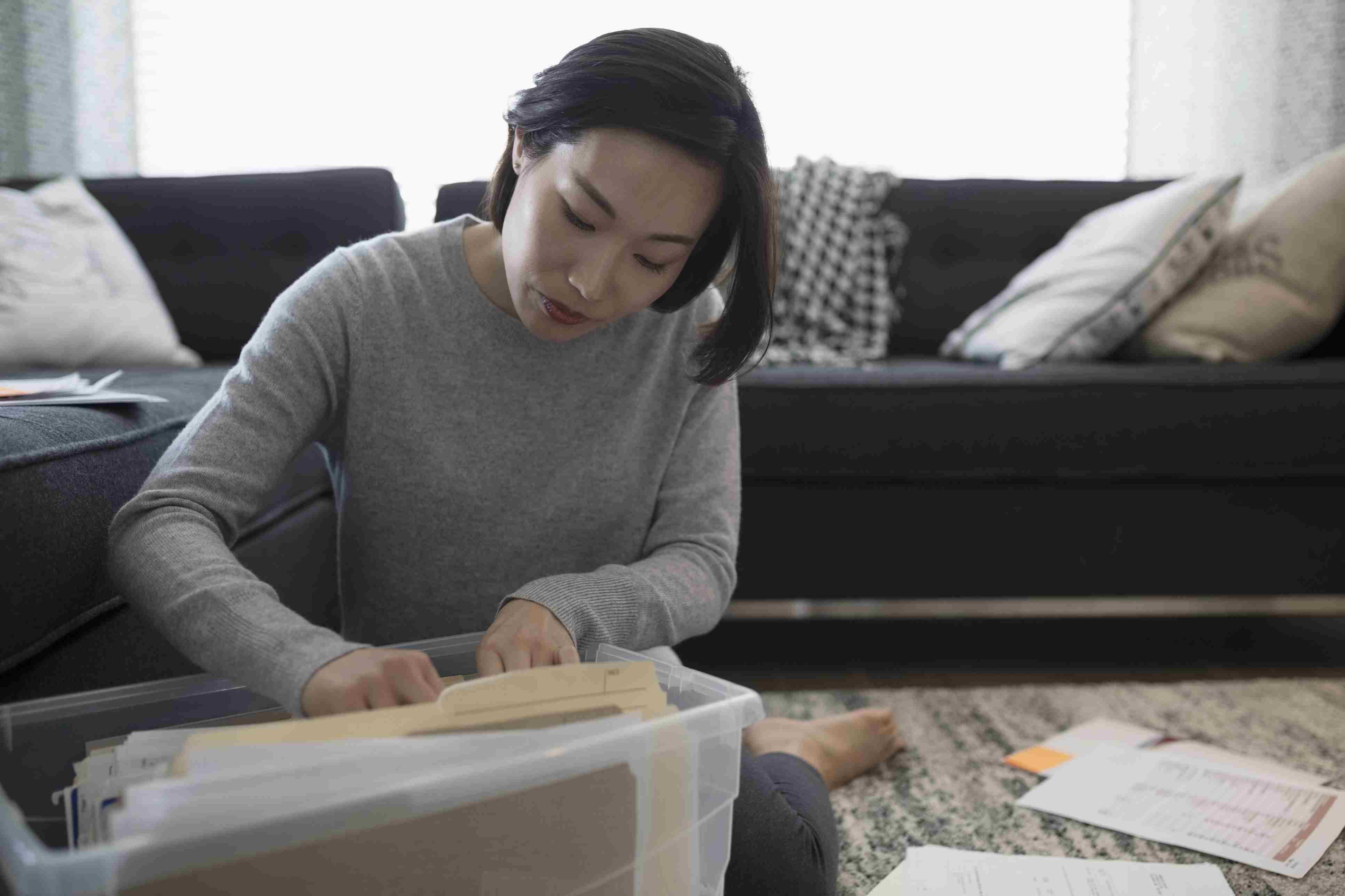 Mujer que presenta documentos financieros mientras está sentada en el piso de la sala de estar. Maquillaje colocado en recipientes de almacenamiento transparentes