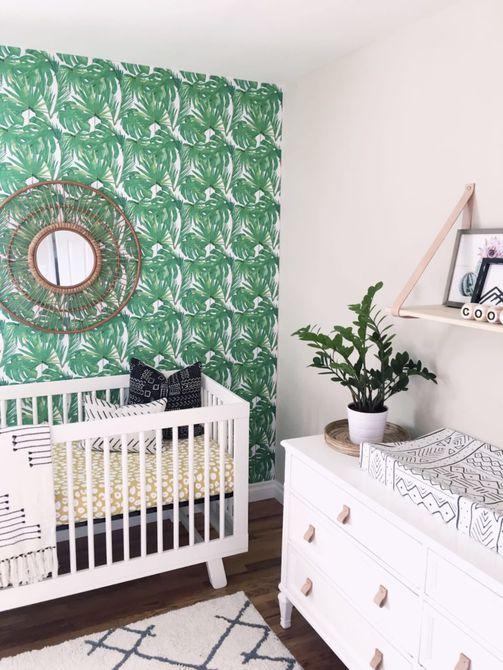 Vivero con pared de acento verde con estampado tropical y acentos amarillos