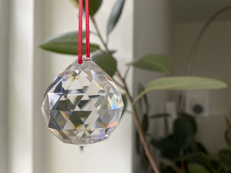 feng shui faceted crystal ball on a red string with a plant