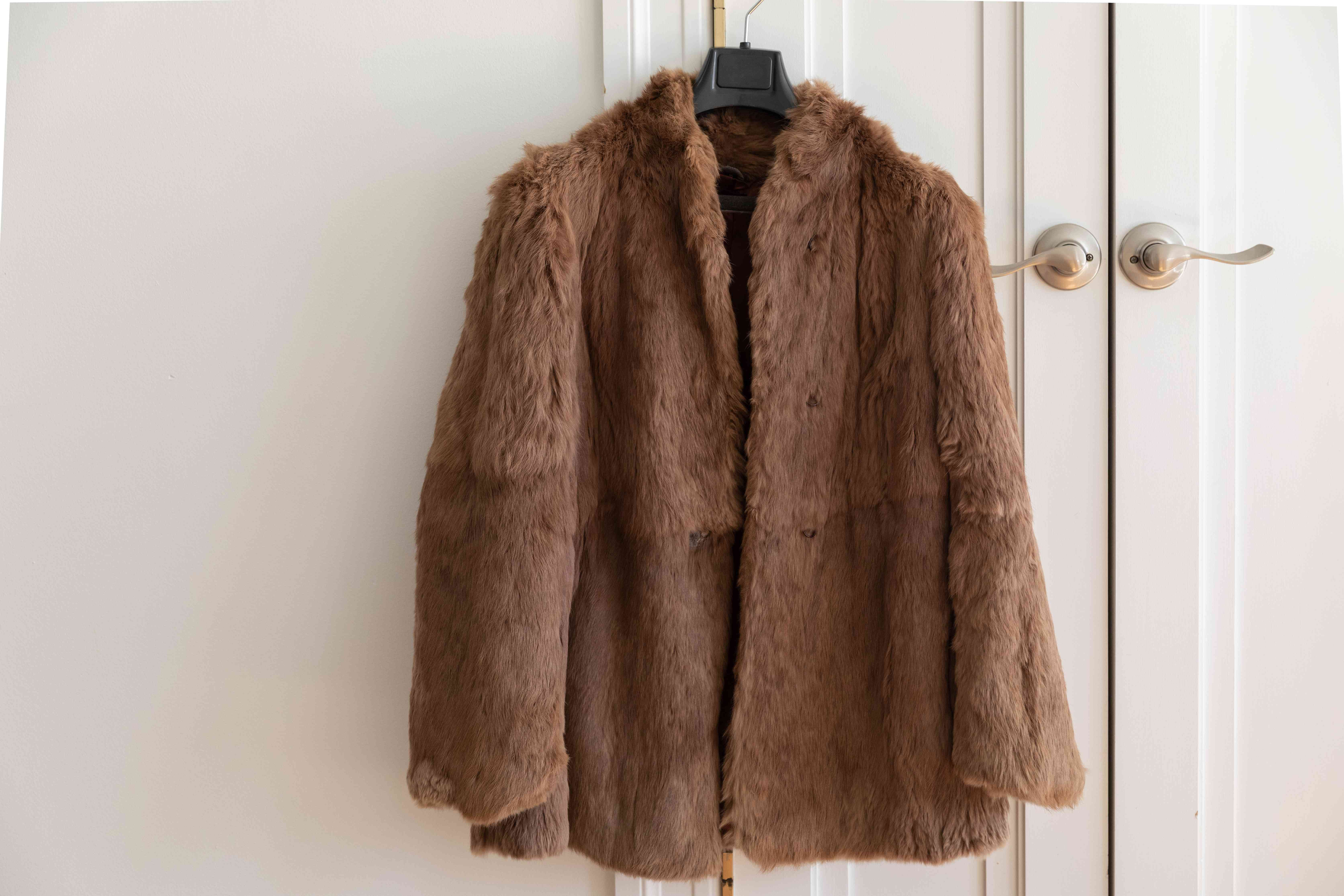 A brown fur coat hanging up to dry