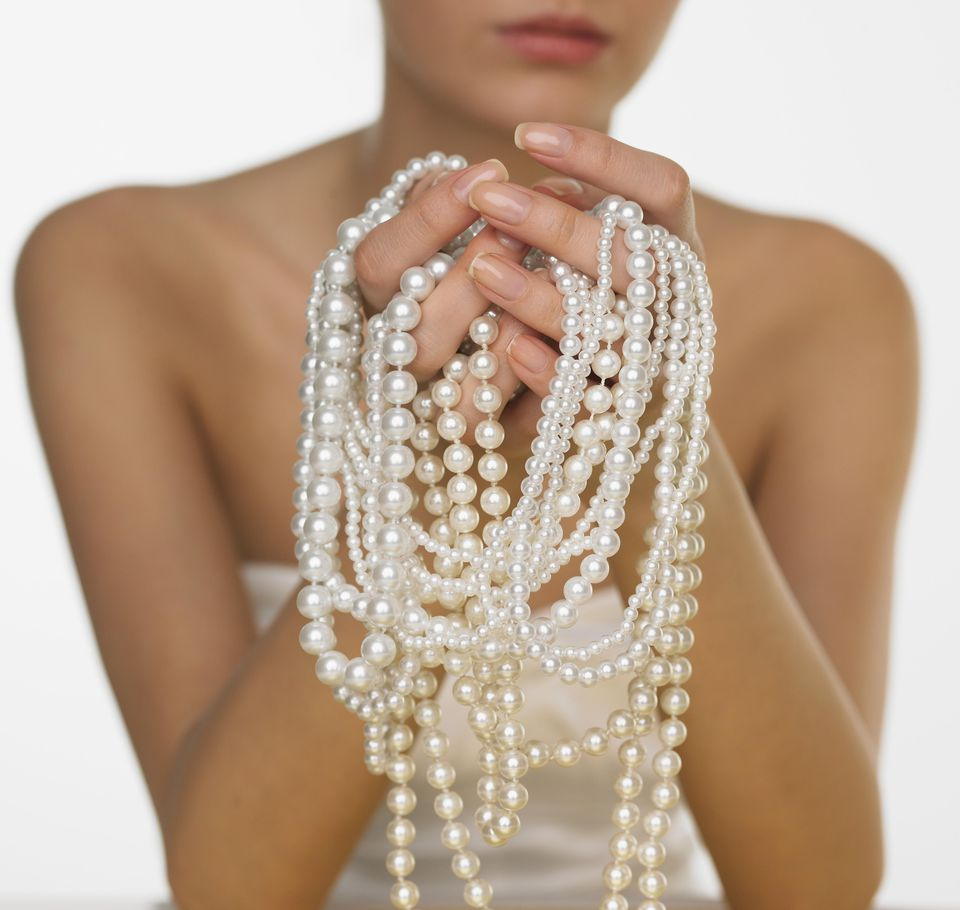 Woman holding pearls, mid section, close-up