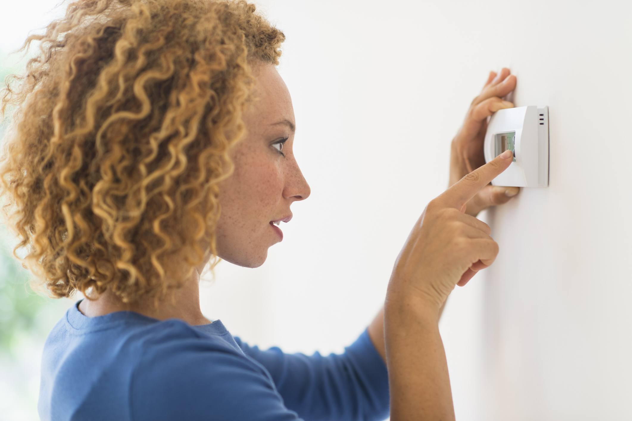 Young woman setting air conditioning