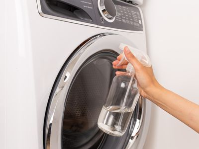 person cleaning a front-load washer