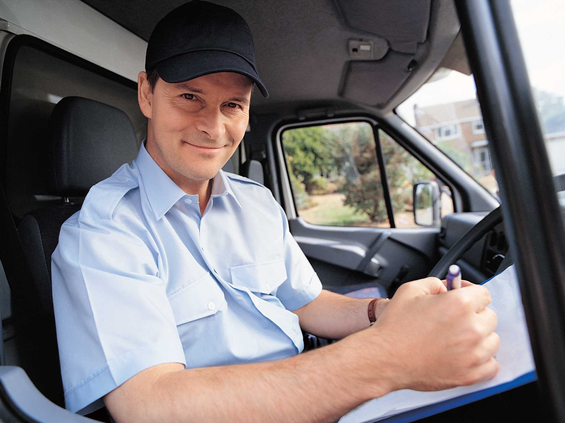 A mover sitting in his truck with paper work