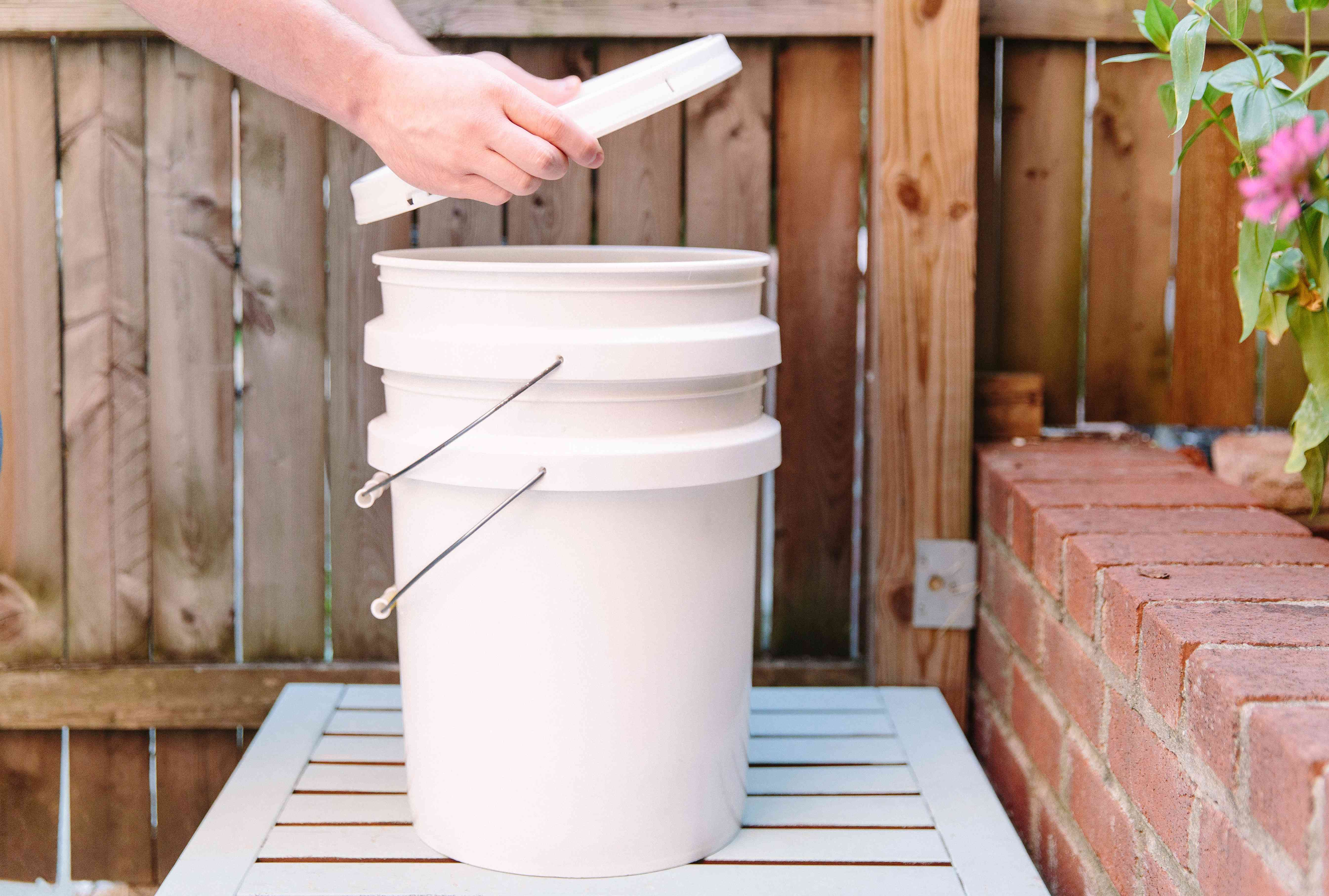 putting the lid with holes on the bucket