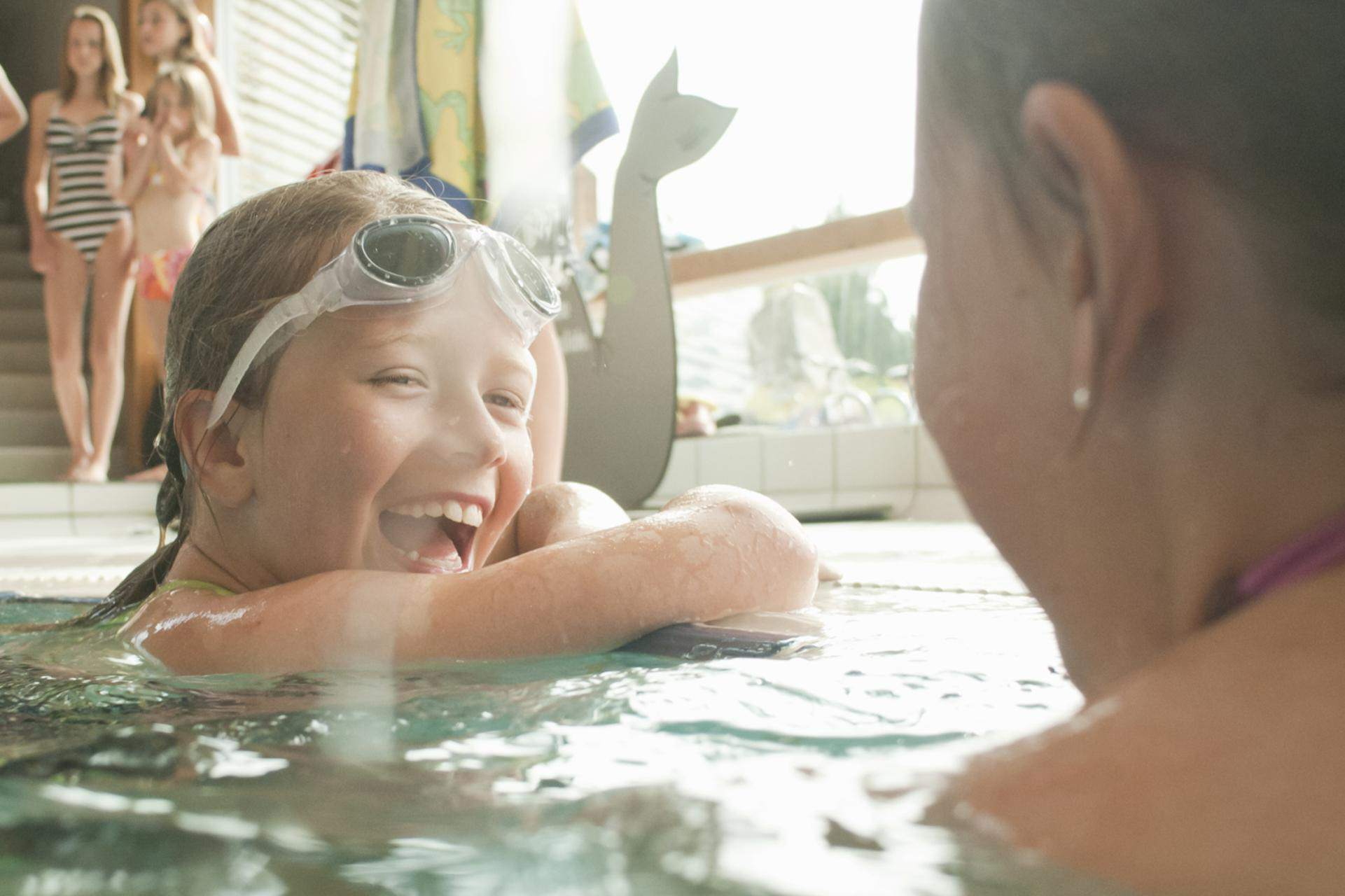 Tween girls laugh in pool.