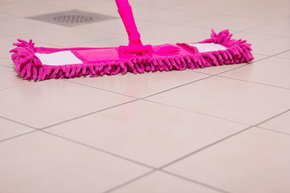 Pink mop cleaning light tile floor in bathroom