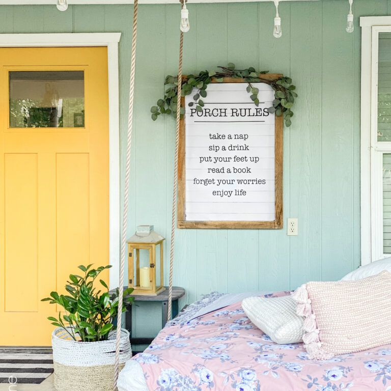 A front porch with a bed and yellow door