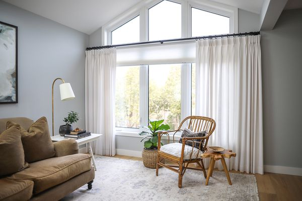 Cathedral windows draped with white curtains on either side by decorated living room