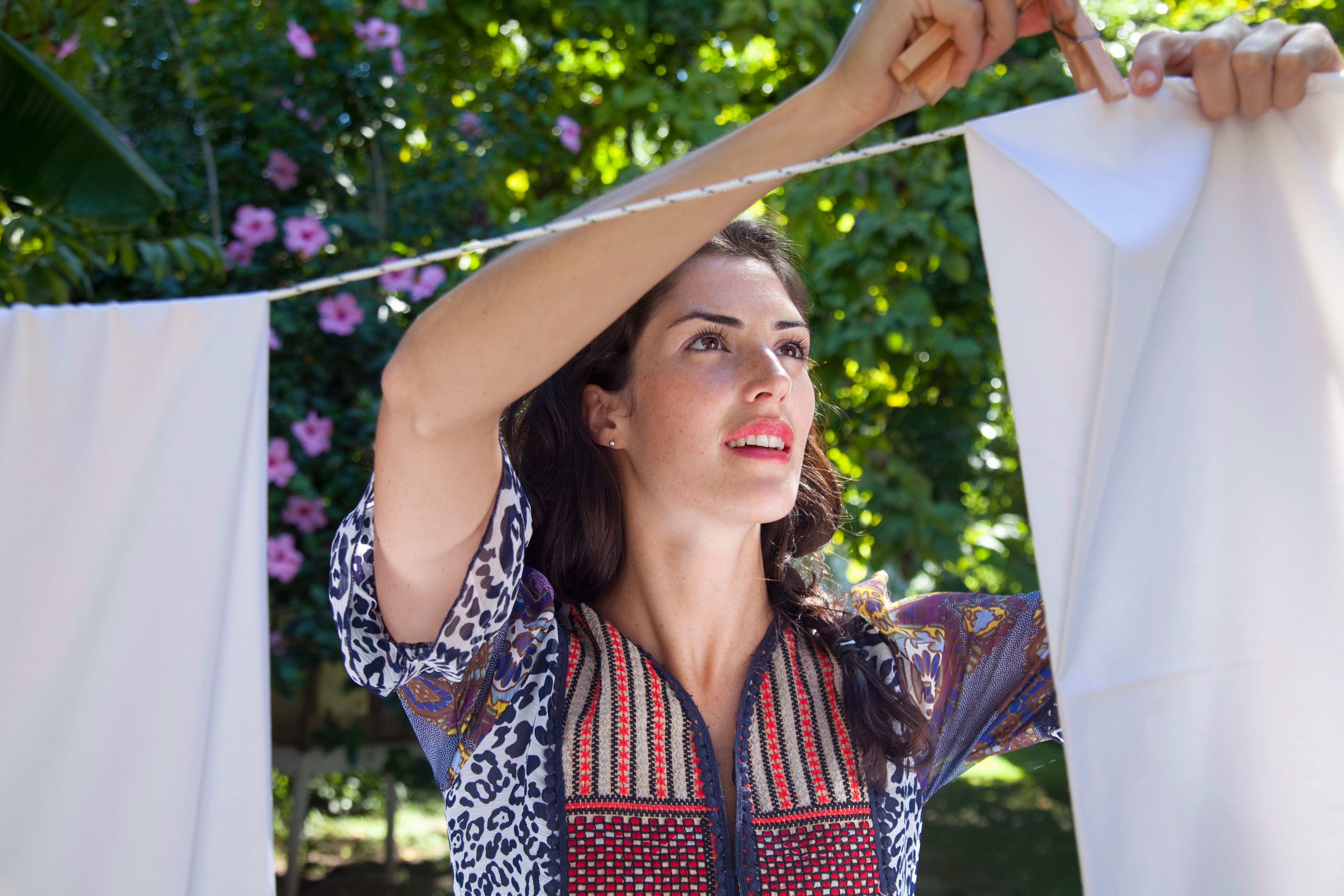 Woman hanging laundry on an outside clothesline.