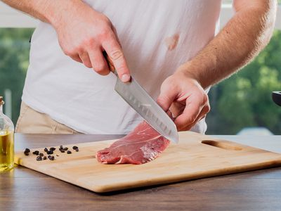 person slicing meat with visible stain on their shirt