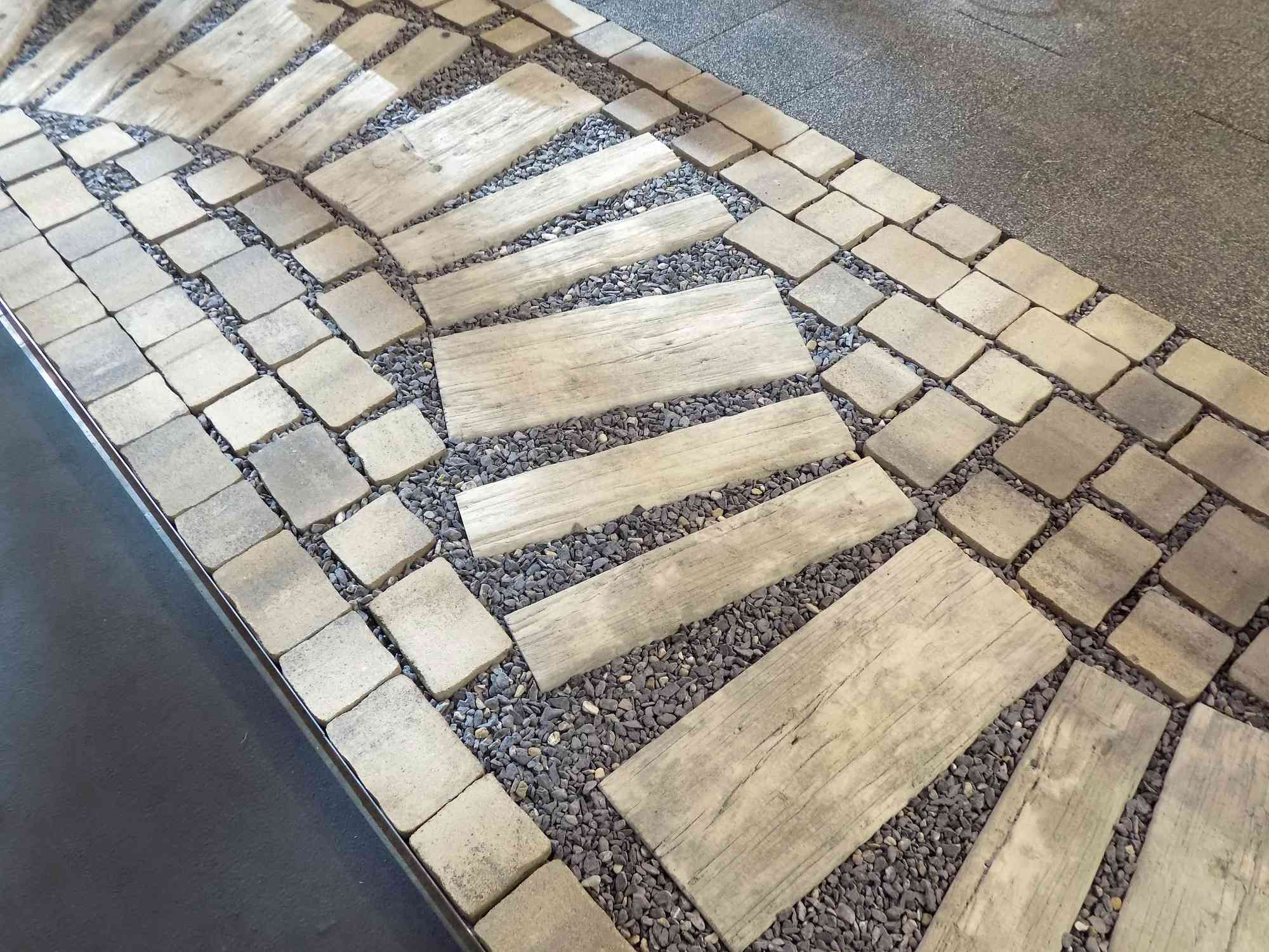A garden walkway made with pavers, gravel and wood slabs.