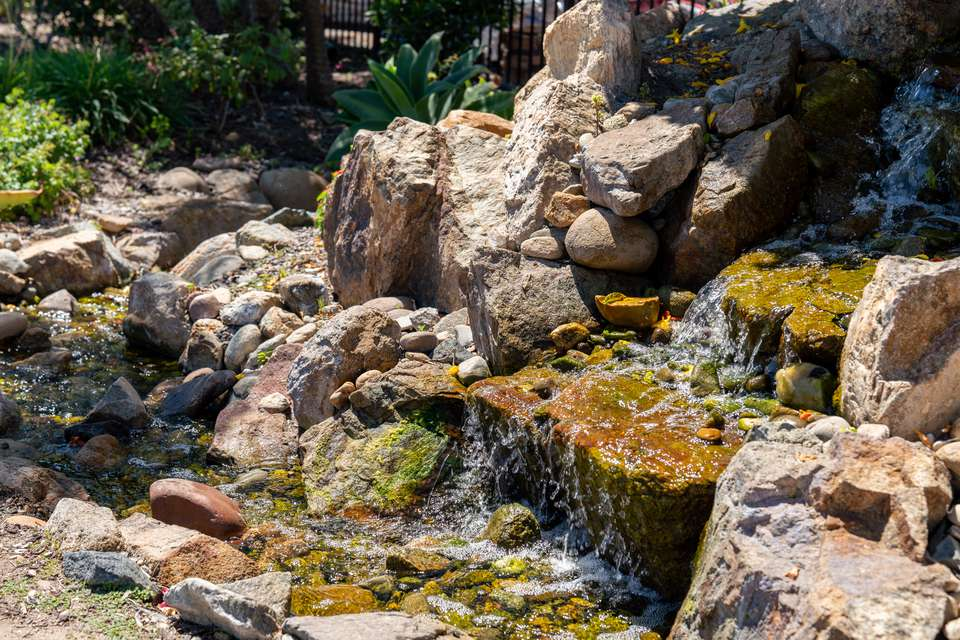 Outdoor waterfall with large rocks and water cascading down to stream