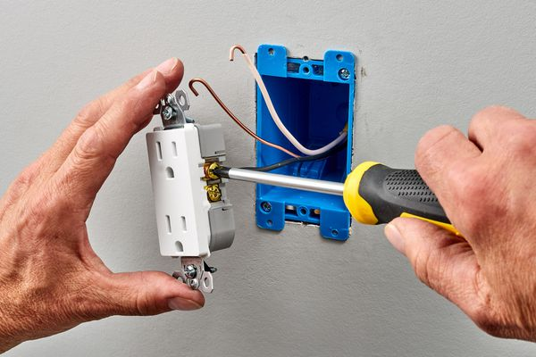 Electrical outlet being rewired with screwdreiver