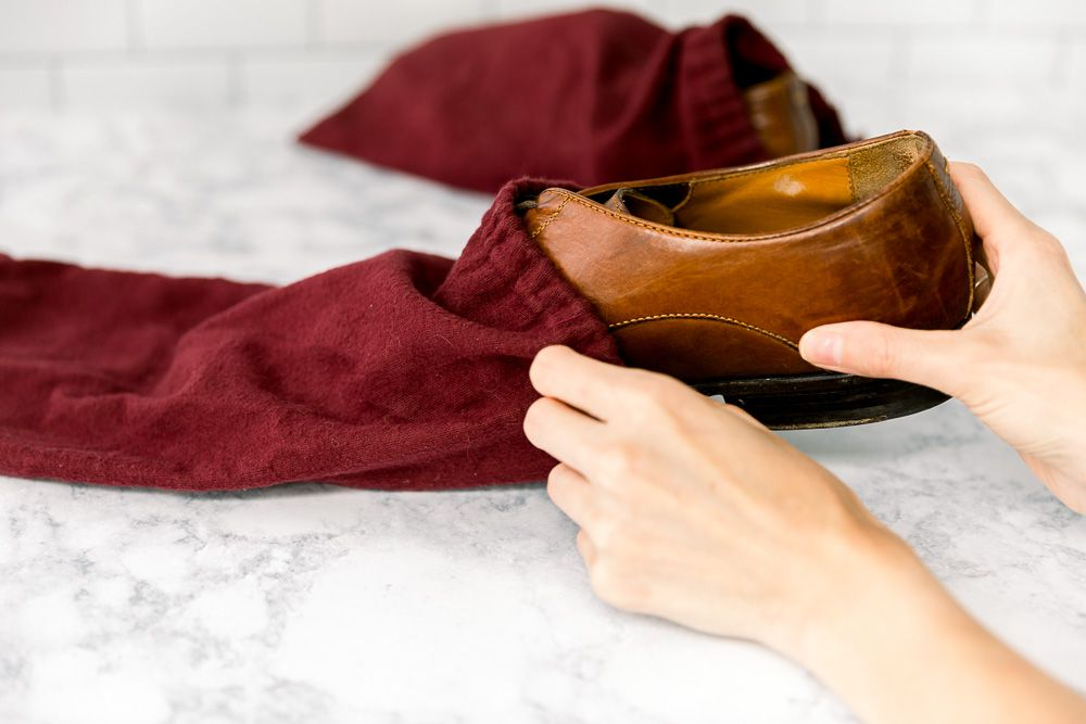 Someone storing leather shoes in cloth bags