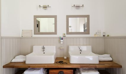 Ikea basin units rest on a wooden shelf with another below for storage in bathroom wth tongue and groove wall panelling