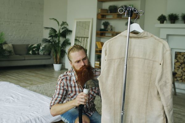 Man steaming his jacket in bedroom at home