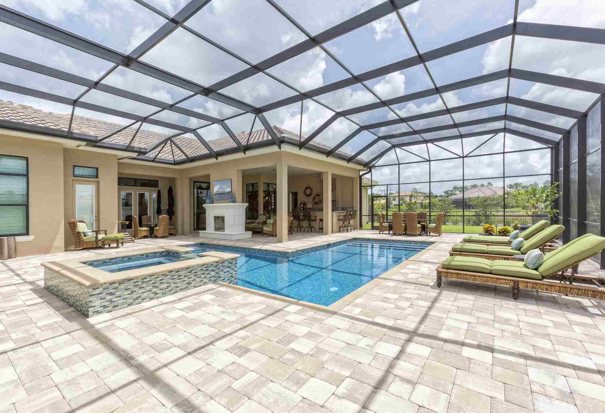 Una piscina cubierta con vidrio techo y baldosas, así como muebles de patio verdes