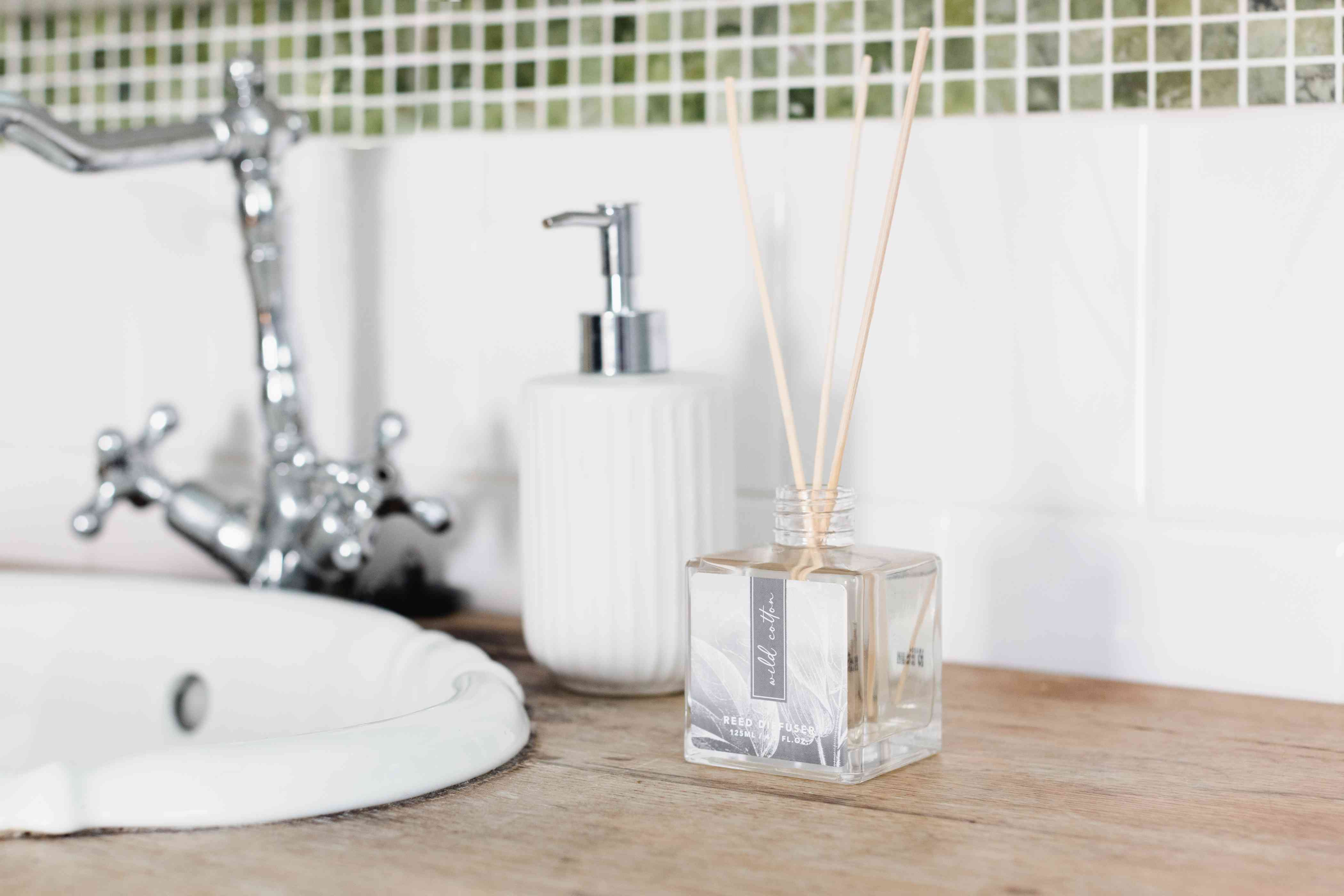 Air freshener with diffuser sticks on bathroom vanity surface