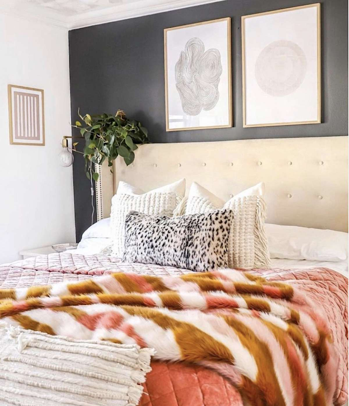 bedroom with dark walls, taller headboard, photos on top half
