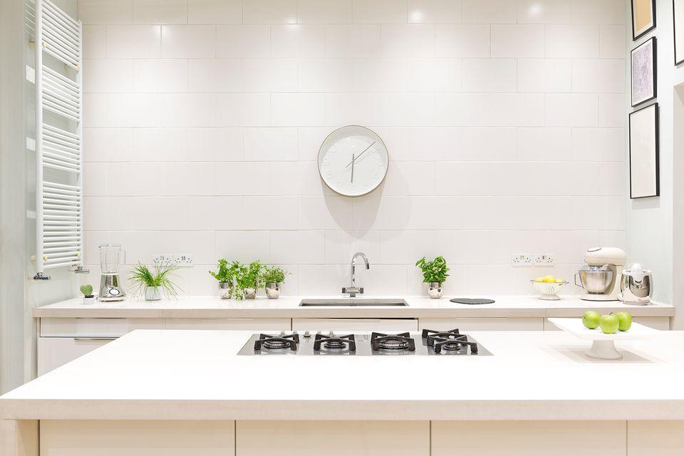 White, modern luxury home showcase interior kitchen with clock