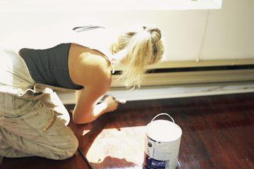 Woman Priming Baseboard Before Painting