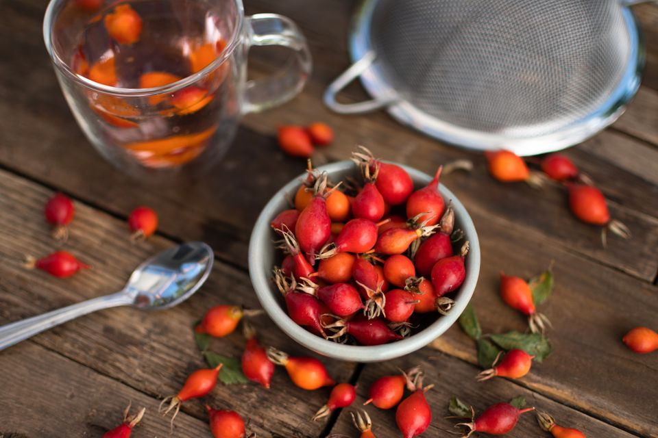 Harvested rose hips in small white bowl next to cup, spoon and strainer