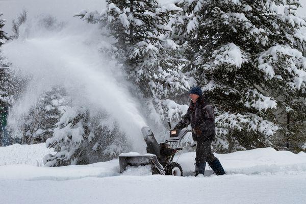Man using snowblower in winter storm