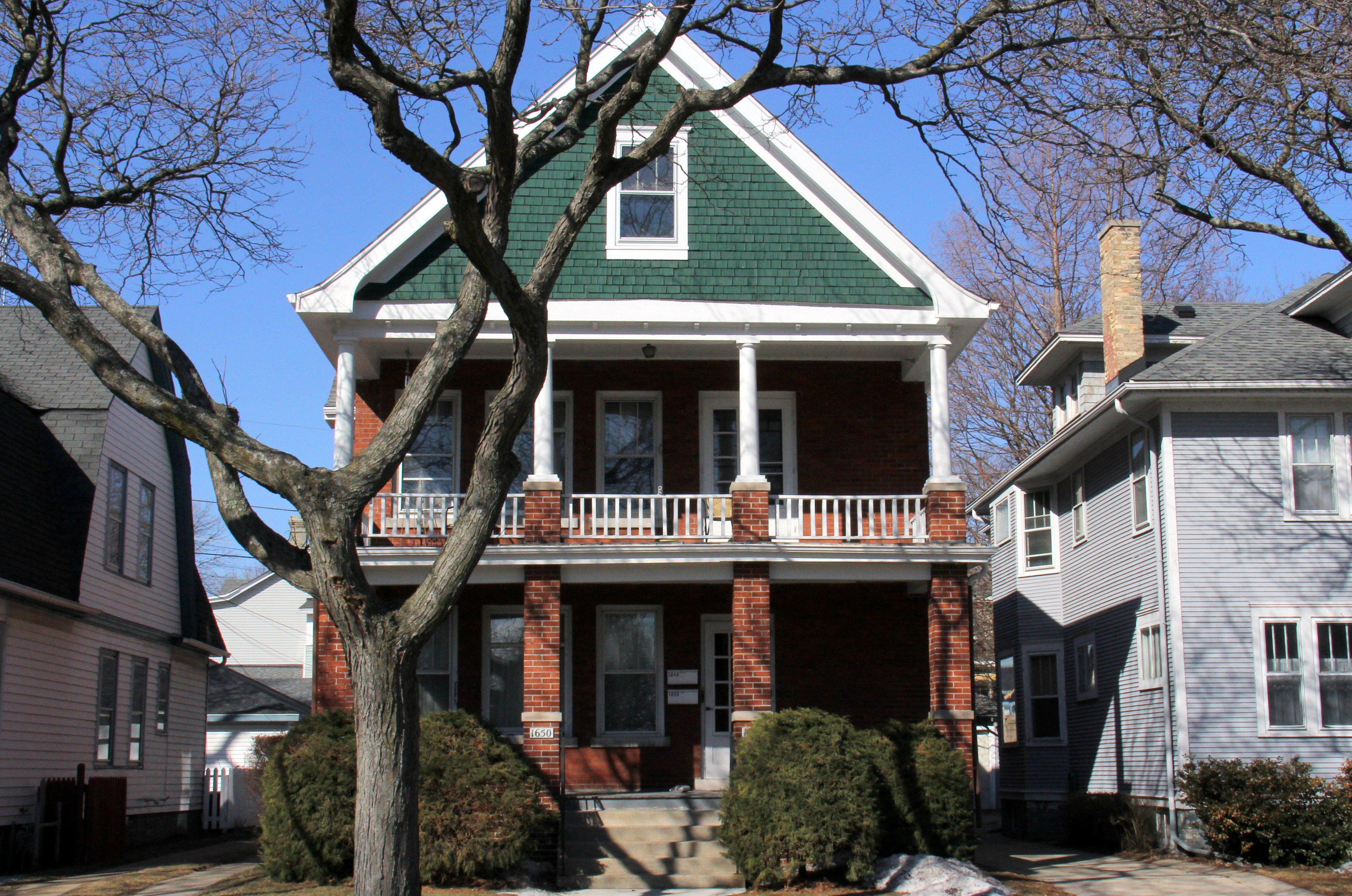Qué Los colores combinan con el ladrillo: un gablete verde contrasta con los porches de ladrillo rojo de esta casa de dos familias.