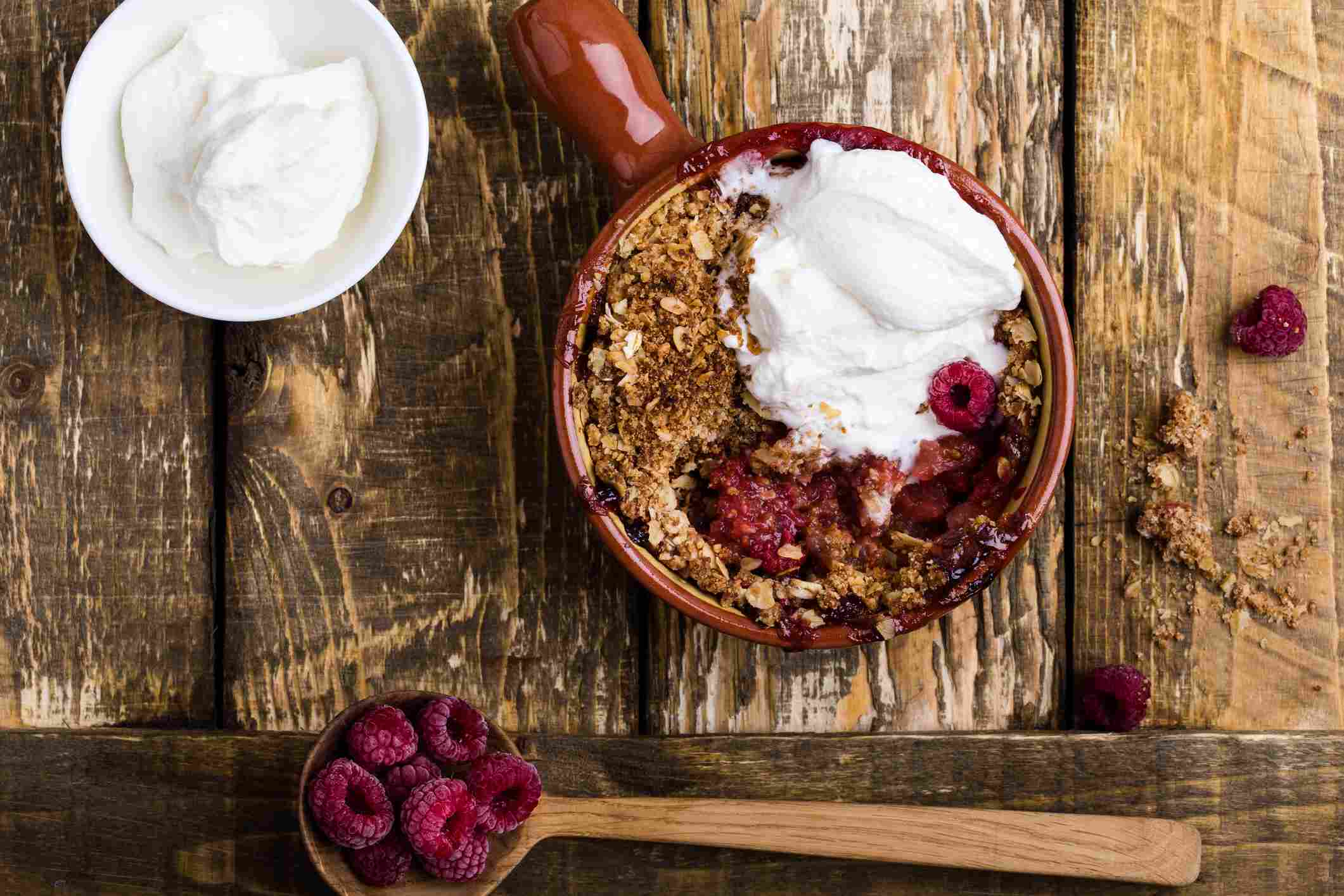 An overhead shot of a raspberry crisp with whipped cream.