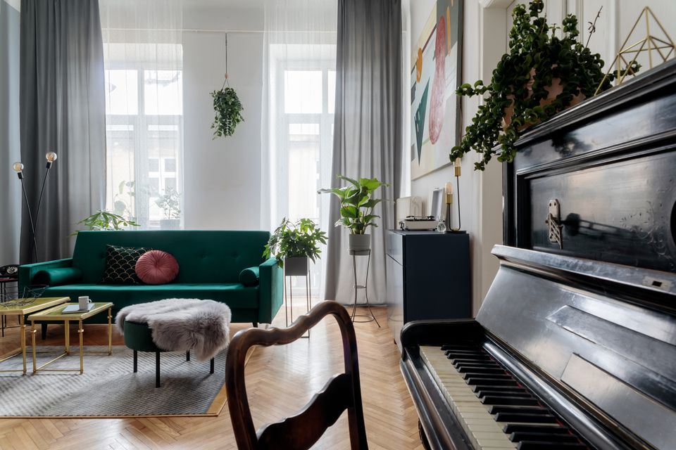Bright and sunny luxury home interior with design green velvet sofa, armchair, table, commode, pouf and accessroies. Big windows. A lot of plants. Stylish decor of living room. View from the piano.