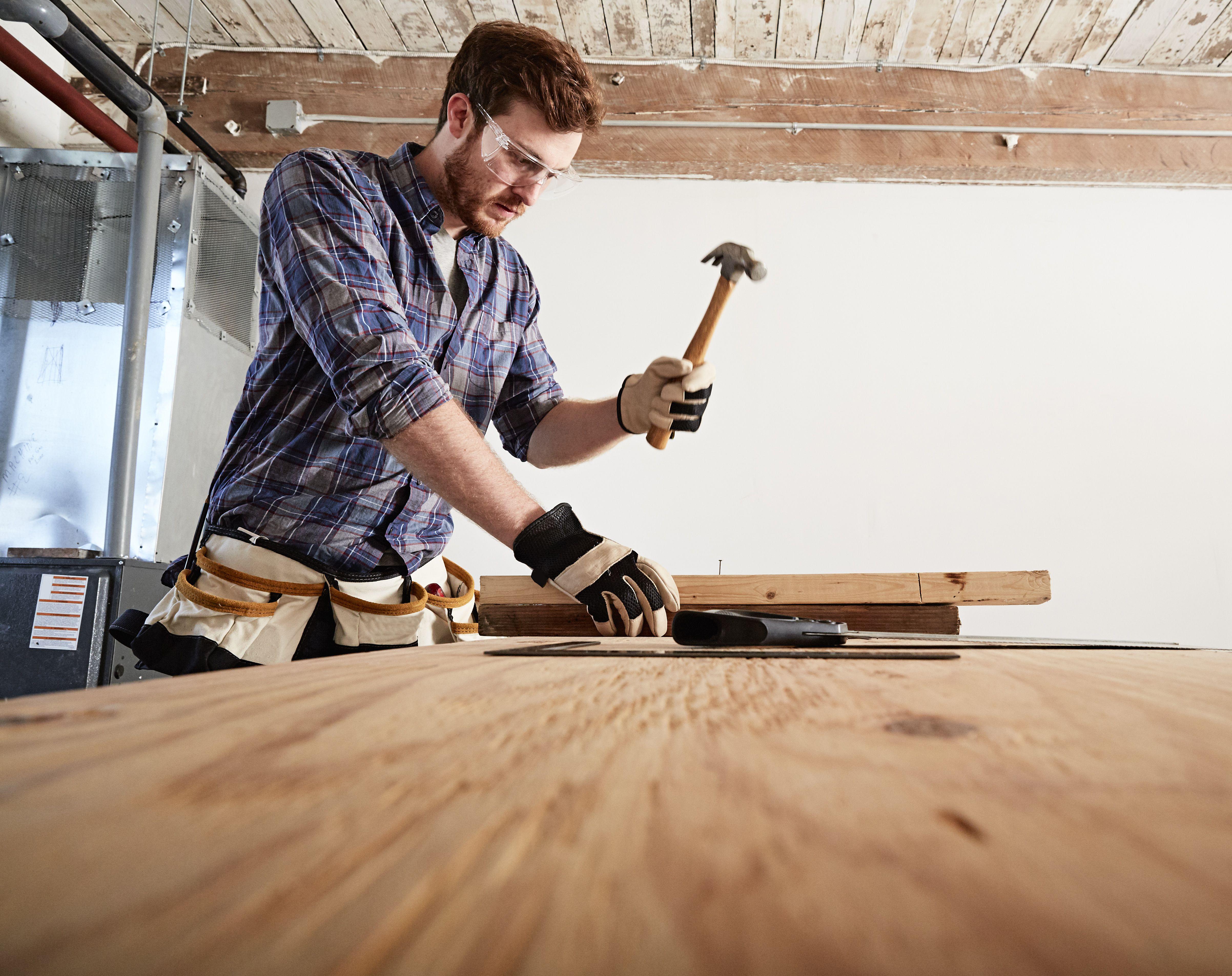 Carpenter in workshop using hammer