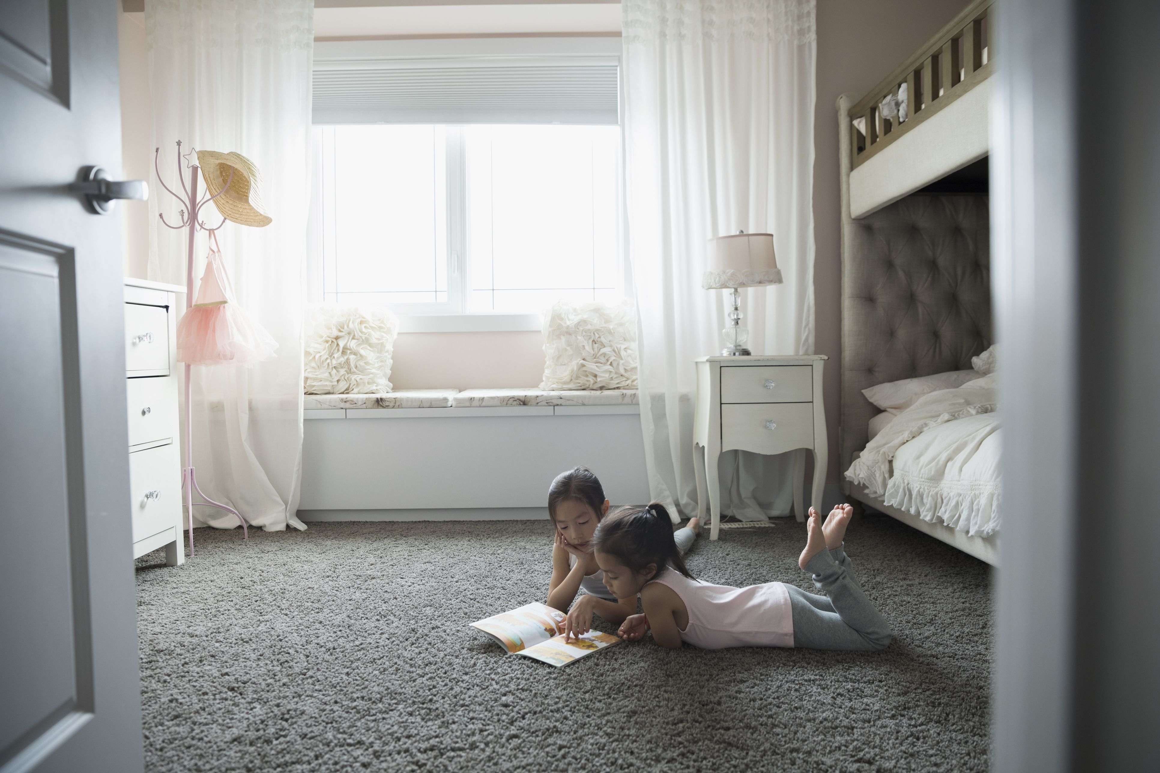 Sisters reading book on carpet in bedroom