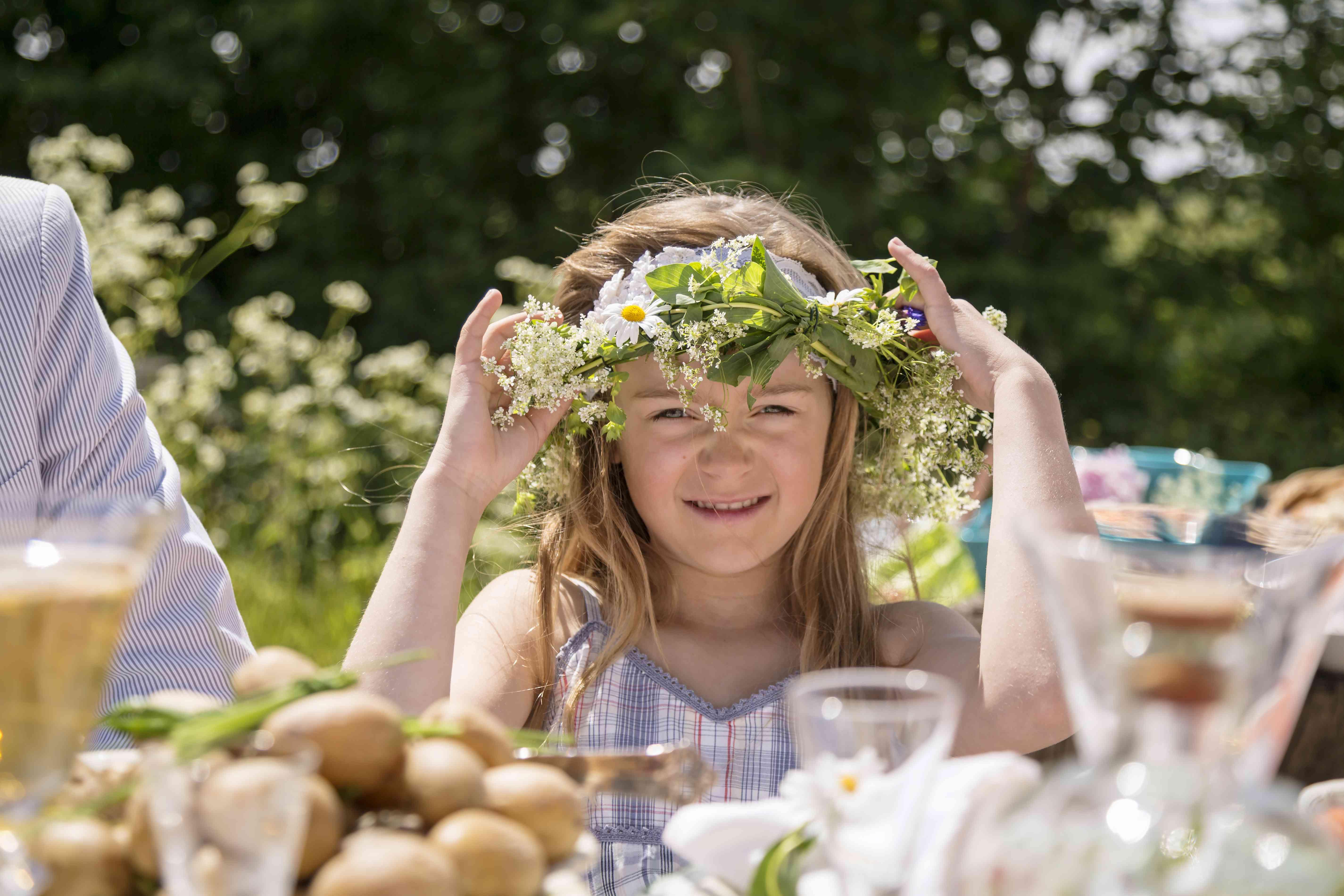 Sweden, Skane, Portrait of girl (8-9) adjusting flower wreath