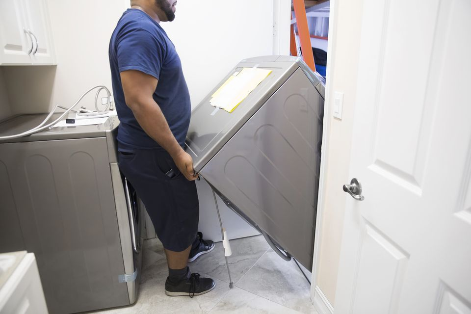Man installing new washer and dryer