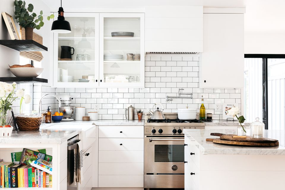 Modern white kitchen decorated with brick wall behind stainless steel oven