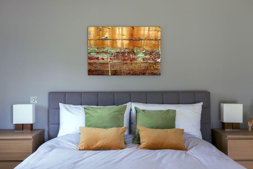 Cama y arte de pared en dormitorio moderno