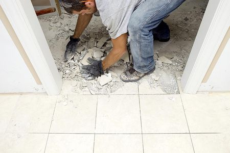 A Construction Worker Is Picking Up Marble Tile Which Has Been Demolished Between An Interior Doorway