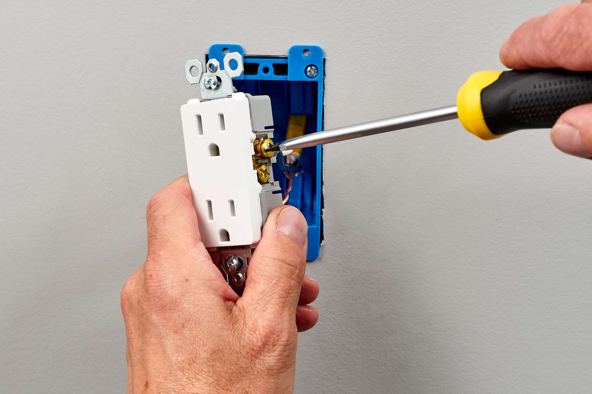 Neutral wire secured in screw terminal of receptacle with screwdriver