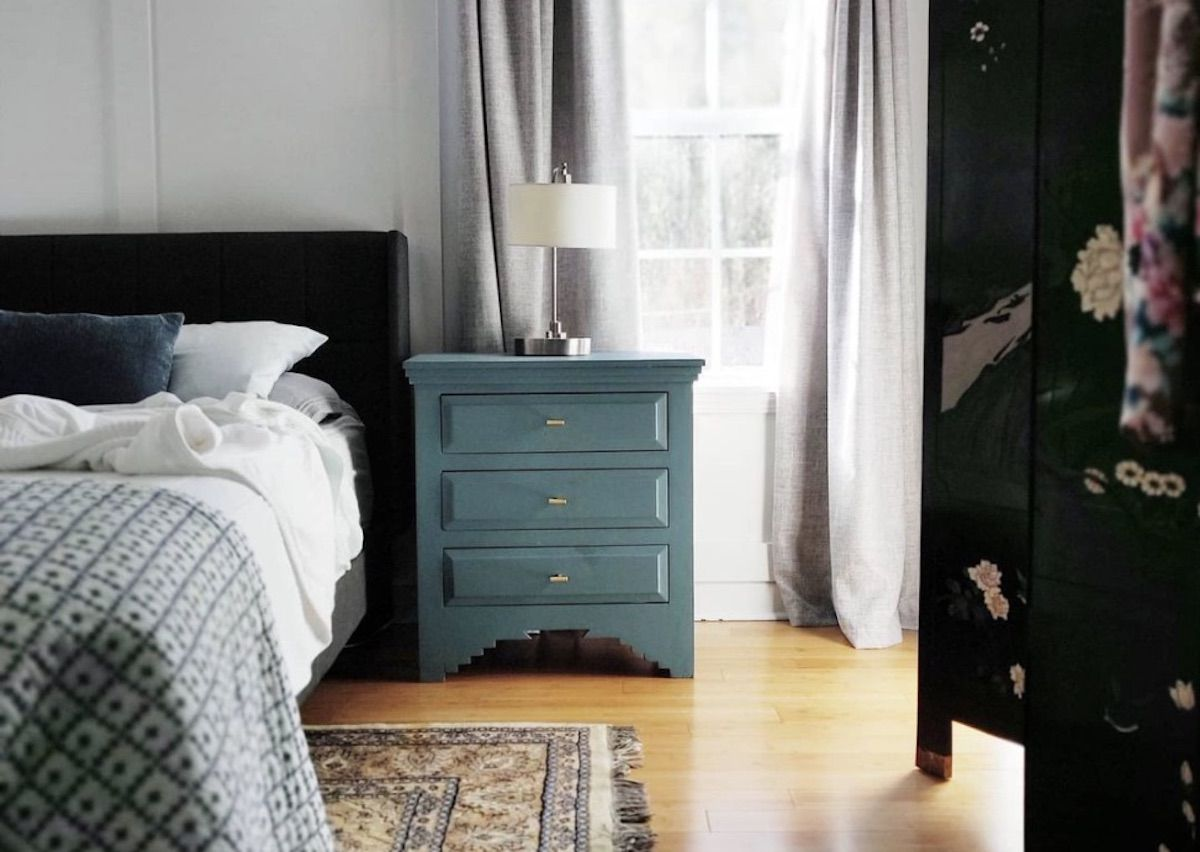 bedroom with bare wooden floors, teal side table, blue bedding, thrifted pattern rug on floor, white walls