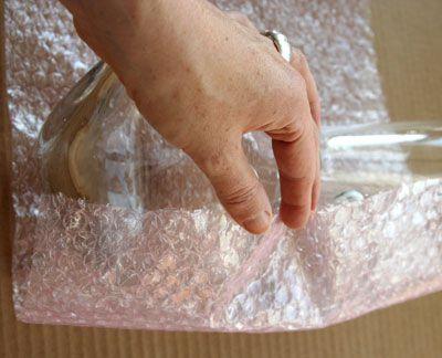 Persona que envuelve una jarra en Bubble Wrap